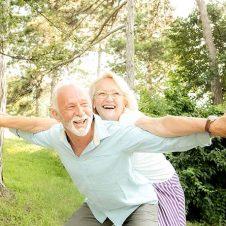 due persone anziane felici in giardino con alberi che trasmettono benessere